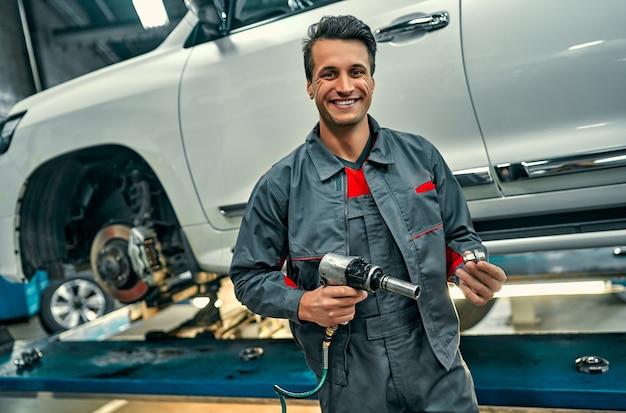 Hübscher mechaniker in uniform arbeitet im autodienst. autoreparatur und wartung. schrauben am rad drehen / aufdrehen.