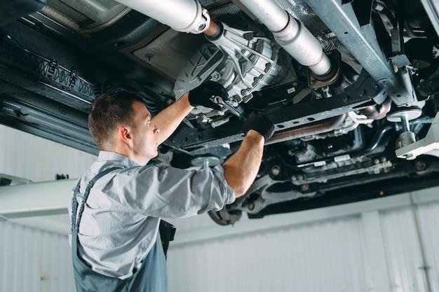 Hübscher mechaniker in uniform, der im autoservice arbeitet