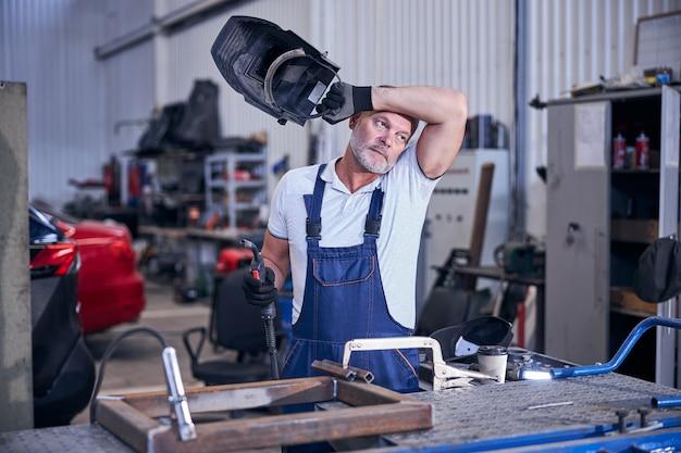 Hübscher mechaniker mit schweißbrenner und schutzhelm