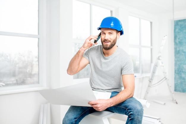 Hübscher mechaniker oder baumeister im helm, der mit telefon mit zeichnungen im weißen innenraum spricht