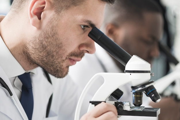 Hübscher mediziner, der mikroskop betrachtet