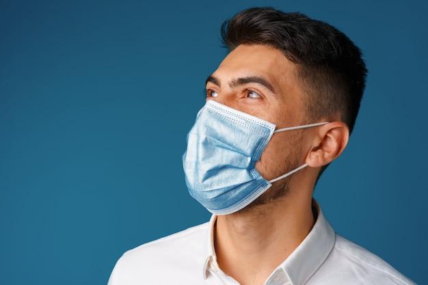 Hübscher mischlingsmann, der medizinische gesichtsmaske nah oben trägt