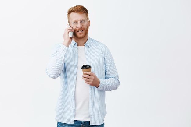 Hübscher moderner geschäftsmann mit roten haaren in gläsern, tasse des getränks haltend und über smartphone lässig über graue wand sprechend