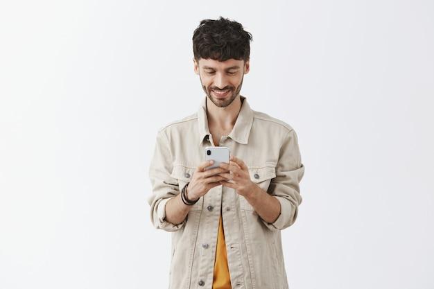 Hübscher moderner kerl, der handy benutzt und lächelt