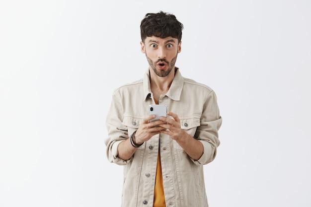 Hübscher moderner kerl, der handy benutzt und überrascht schaut