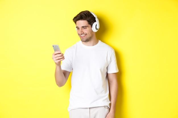 Hübscher moderner kerl, der wiedergabeliste auf smartphone wählt, kopfhörer trägt und über gelber wand steht