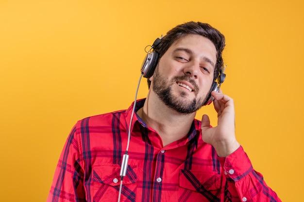 Hübscher moderner mann, der musik in kopfhörern auf gelb hört