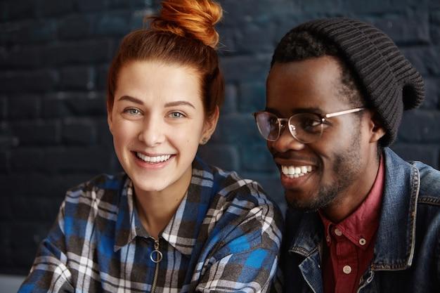 Hübscher modischer afroamerikanischer hipster in hut und brille, die gute zeit verbringen