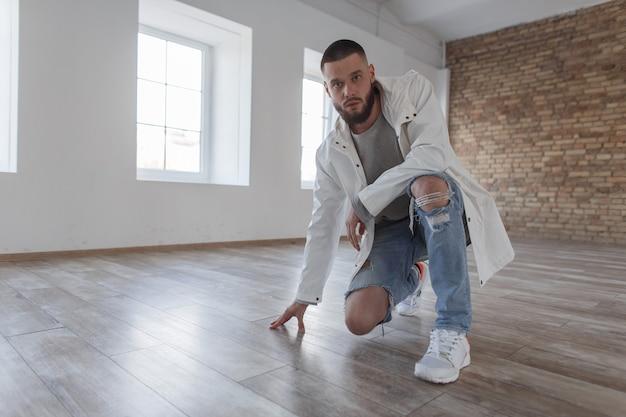 Hübscher modischer junger attraktiver mann in einer modischen jacke mit zerrissenen jeans mit weißen turnschuhen, die die kamera innen aufstellen und betrachten