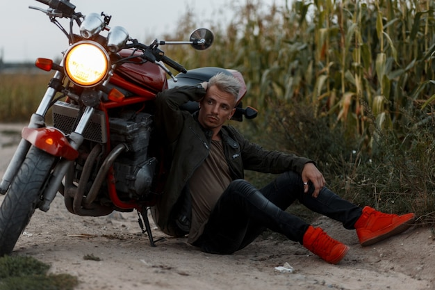 Hübscher modischer junger mann in einer modischen militärjacke mit turnschuhen sitzt am abend in der nähe eines motorrads mit licht in einem getreidefeld