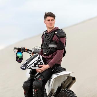 Hübscher motorradfahrer, der helm hält
