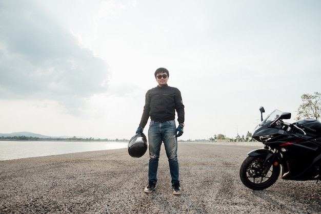 Hübscher motorradfahrer mit sturzhelm in den händen des motorrades