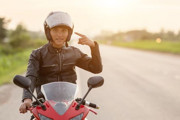 Hübscher motorradfahrer zeigen mit dem finger auf seinen helm