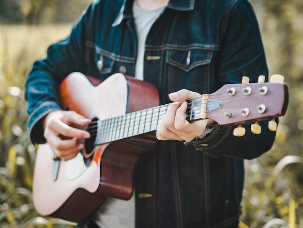 Hübscher musiker, der akustikgitarre am rasenflächenunschärfehintergrund spielt.
