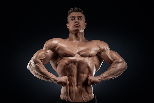 Hübscher muskulöser bodybuilder, der auf front lat spread aufwirft