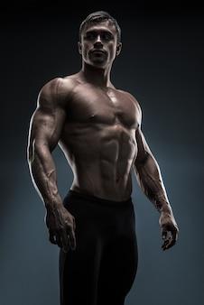 Hübscher muskulöser bodybuilder, der über schwarzem hintergrund aufwirft