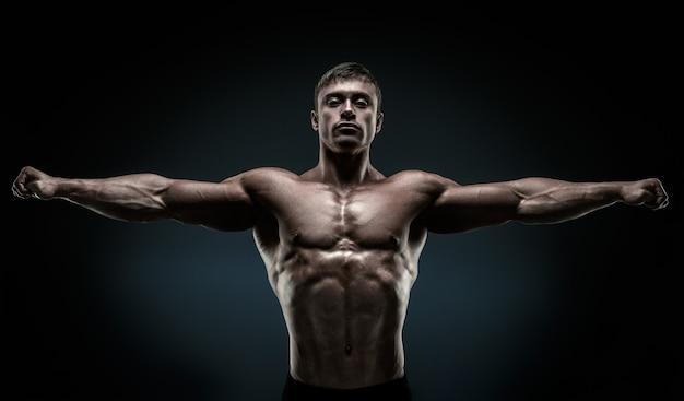 Hübscher muskulöser bodybuilder posiert und hält die arme ausgestreckt. muskulöser und fitter junger bodybuilder, der seine hände auf schwarzem hintergrund aufwirft.