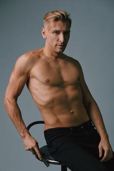 Hübscher muskulöser junger mann, der am studio aufwirft
