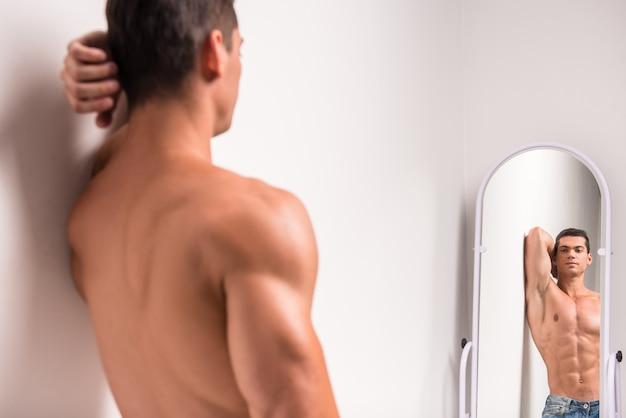 Hübscher muskulöser mann betrachtet sich im spiegel.
