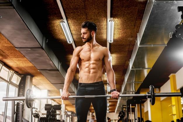 Hübscher muskulöser mann, der im fitnessstudio arbeitet.