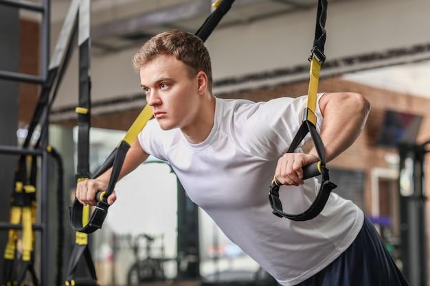 Hübscher muskulöser mann, der mit trx-trägern im fitnessstudio trainiert