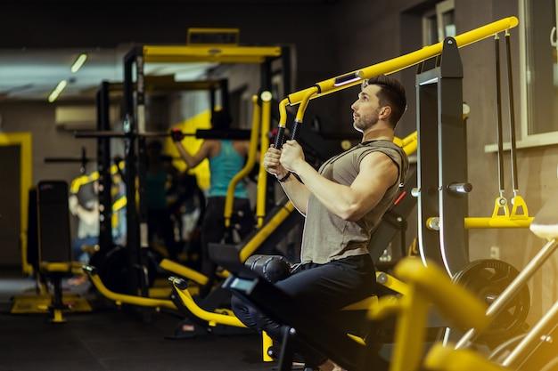 Hübscher muskulöser mann, der stark an der turnhalle ausarbeitet