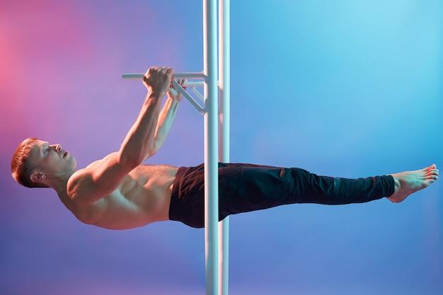 Hübscher muskulöser mann, der übungen auf horizontaler stange macht