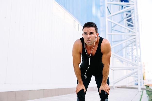 Hübscher muskulöser mann im kopfhörer, der nach dem laufen, während des trainings draußen stillsteht