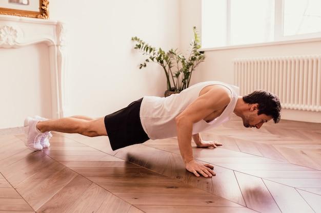 Hübscher muskulöser mann in einem t-shirt und in den shorts, die funktionelle übungen auf dem boden zu hause machen