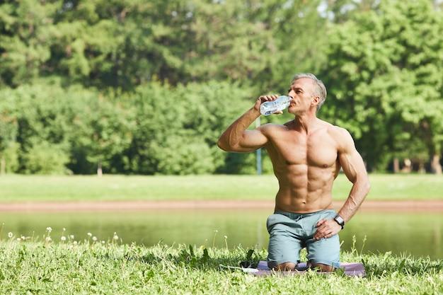 Hübscher muskulöser mann mit bauchmuskeln auf bauch, der auf matte im park sitzt und wasser von flasche trinkt
