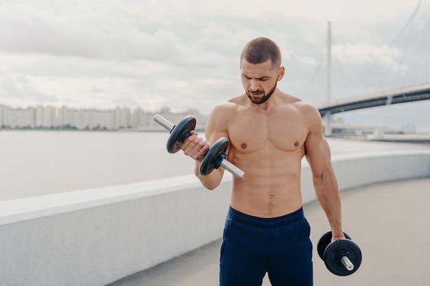 Hübscher muskulöser mann mit nacktem oberkörper im freien, der fitness-training tut