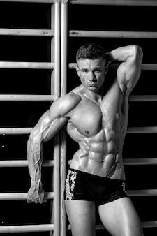 Hübscher muskulöser mann ohne hemd, der weiße hosen trägt, vor der betonwand