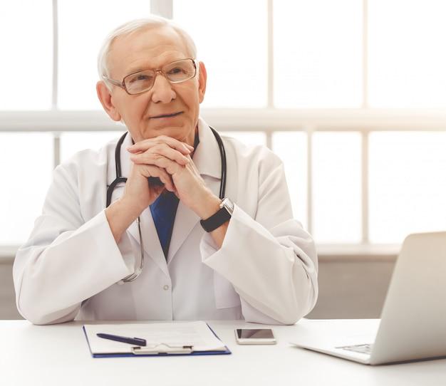 Hübscher nachdenklicher alter doktor im weißen medizinischen mantel