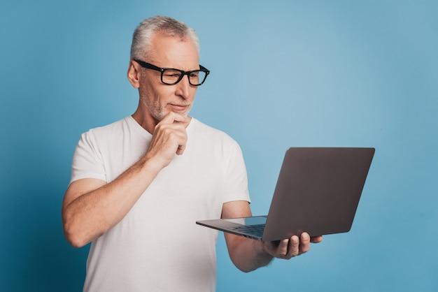 Hübscher nachdenklicher alter mann mit laptop auf blauem hintergrund isoliert