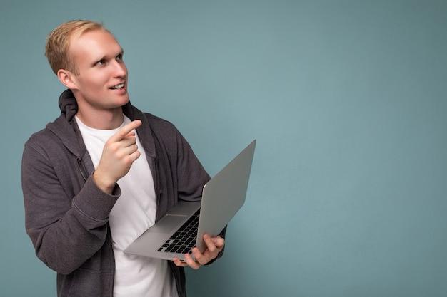 Hübscher nachdenklicher blonder mann mit computerlaptop