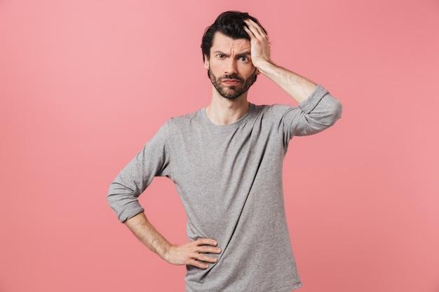 Hübscher nachdenklicher junger bärtiger brünetter mann, der pullover trägt, der über rosa steht und denkt