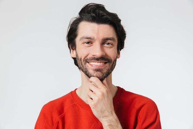 Hübscher nachdenklicher junger bärtiger brünetter mann, der pullover trägt, der über weiß steht und denkt
