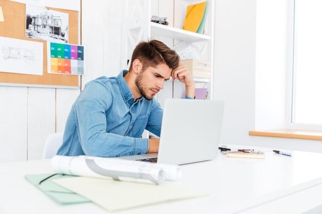 Hübscher nachdenklicher junger geschäftsmann, der laptop im büro arbeitet und benutzt