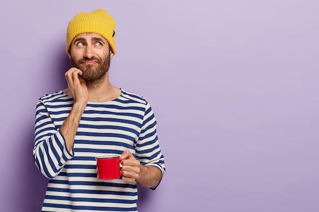 Hübscher nachdenklicher junger mann mit borsten, hält eine tasse kaffee, hat nachdenklichen blick, pause nach der arbeit, trägt gestreiften pullover, gelbe kopfbedeckung