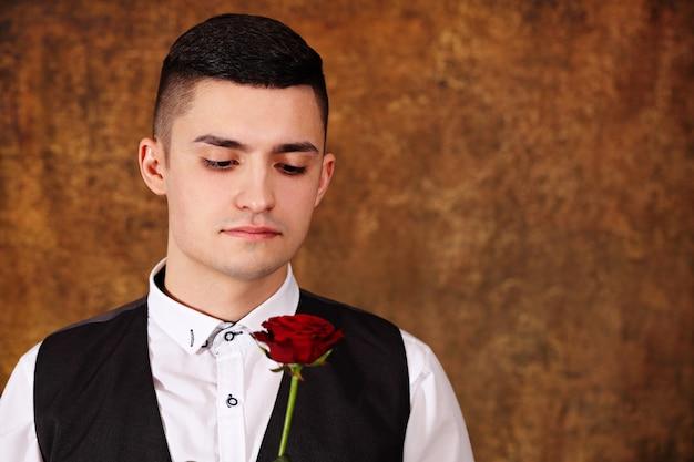 Hübscher nachdenklicher kerl in einer schwarzen weste mit einer rose in seinen händen am valentinstag