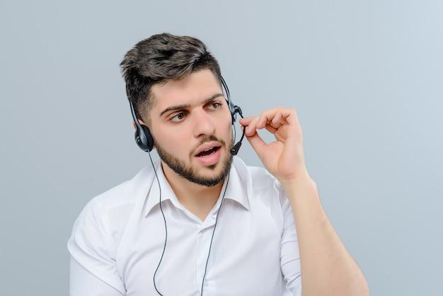 Hübscher nahöstlicher mann, der mit antwortenden geschäftsanrufen des kopfhörers als versender der technischen unterstützung lokalisiert über grauem hintergrund arbeitet