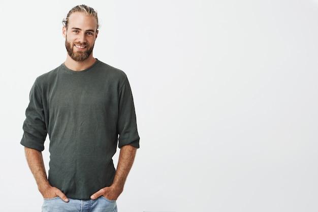 Hübscher nordischer mann mit bart und stilvoller frisur im grauen hemd und in den lächelnden jeans hält hände in den taschen.
