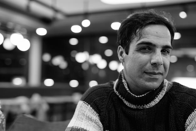 Hübscher persischer mann, der am kaffeehaus in schwarzweiss entspannt