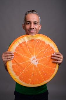 Hübscher persischer mann mit grauem haar, das große orangenscheibe hält