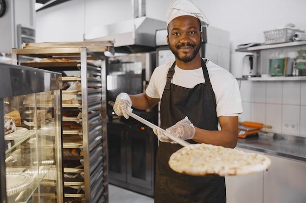 Hübscher pizzaiolo, der pizza in der küche in der pizzeria macht. afroamerikanische ethnizität.
