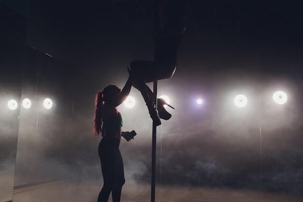 Hübscher pole fitness instructor, der einen ihrer schüler während des unterrichts unterstützt.
