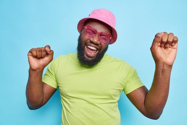 Hübscher positiver bärtiger mann hat spaß auf sommerpartytänzen sorglos hält die arme hoch, trägt rosa panama herzförmige sonnenbrillen und grünes t-shirt isoliert auf blauer studiowand