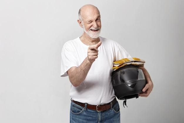 Hübscher positiver emotionaler älterer reifer bärtiger mann mit kahlem kopf, der motorradhelm hält