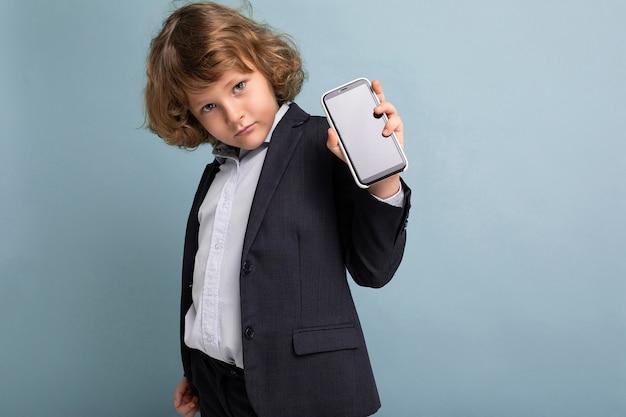 Hübscher positiver ernster junge mit dem lockigen haar, der anzug trägt, der das telefon einzeln auf blauem hintergrund hält, das kamera betrachtet und smartphone mit leerem bildschirm zeigt. ausgeschnitten