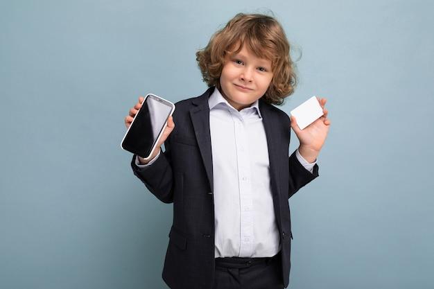 Hübscher, positiver, glücklicher junge mit lockigem haar, der einen anzug trägt, der telefon und kreditkarte hält und den mobilen bildschirm auf die kamera zeigt, die auf blauem hintergrund mit blick auf die kamera isoliert ist?